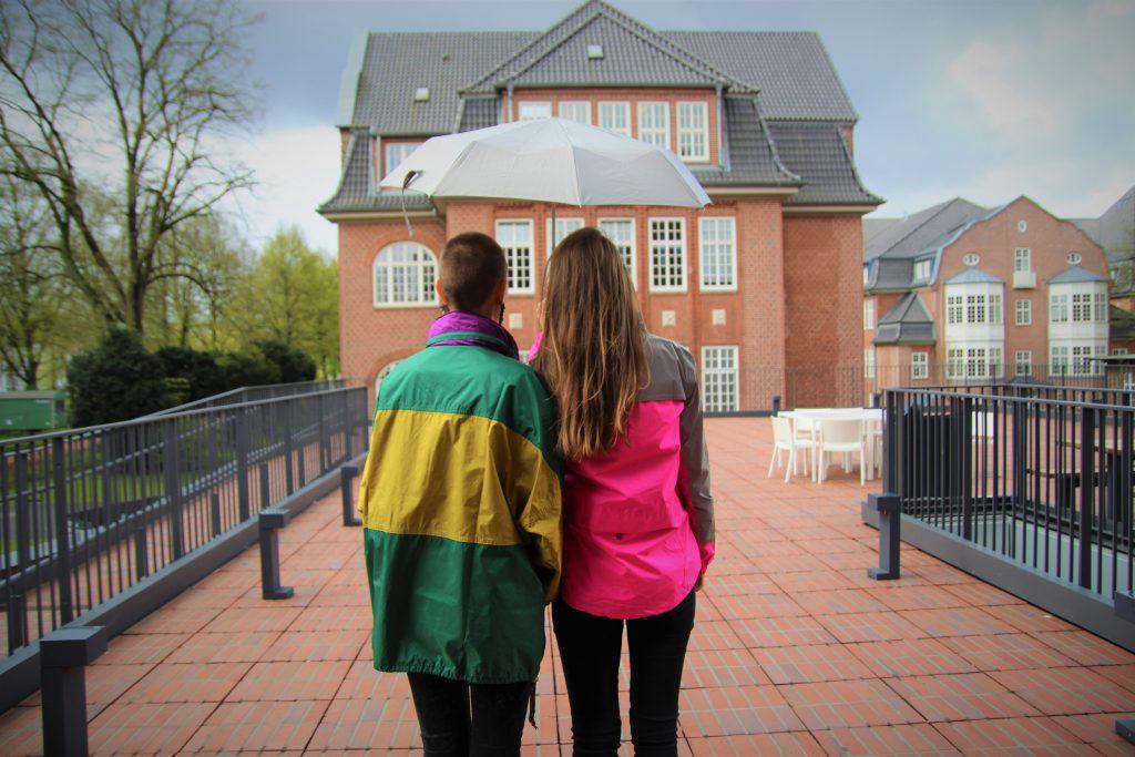 Zwei Mädchen in Regenjacken stehen an einem regnerischen Tag vor einem Gebäude.