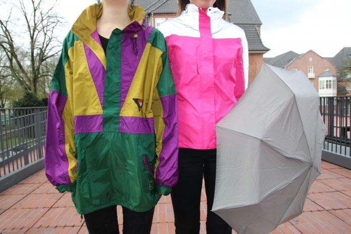 Zwei Frauen in bunten Regenjacken. Die Rechte hält einen Regenschirm.