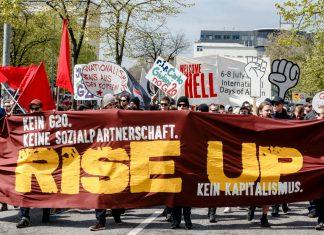 Demonstranten laufen hinter einem Anti-G20-Transparent.