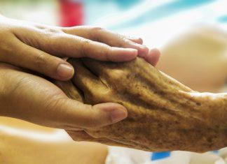 Die Hand eines älteren Menschen wird gehalten.