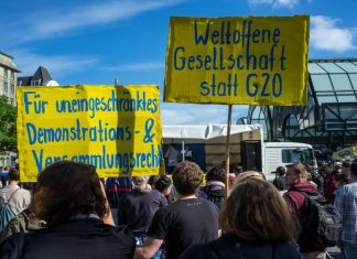 Demonstranten am Hachmannplatz halten Schilder hoch. Die Volkspetition ist erfolgreich.