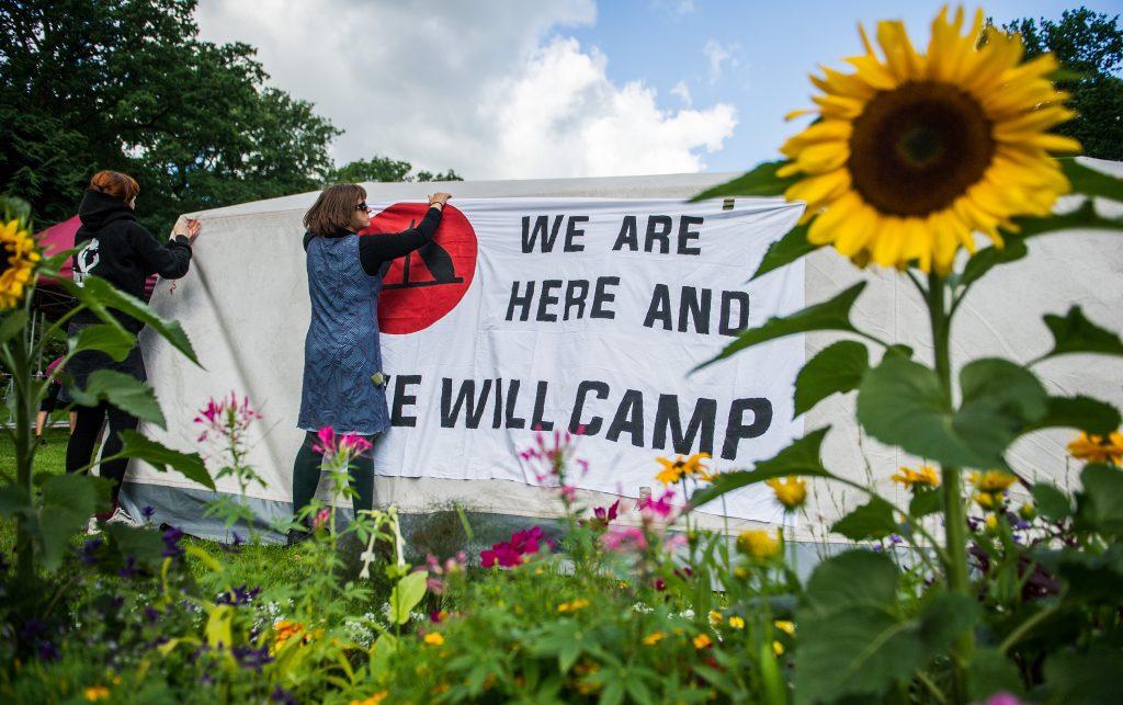 """Unterstützer des """"Antikapitalistischen Camps"""" befestigen Banner im Eingang des Stadtparks. Foto: Christina Sabrowsky/dpa"""