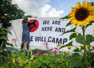 Unterstützer des G20-Protestcamps befestigen Banner im Eingang des Stadtparks. Foto: Christina Sabrowsky/dpa