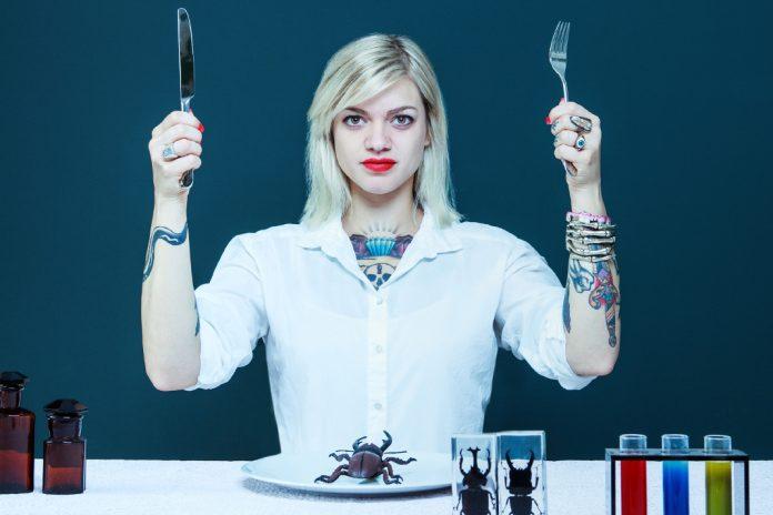 Eine junge, tättowierte Frau, die Messer und Gabel in die Luft hält. Vor ihr Reagenzgläser und Käfer auf dem Teller