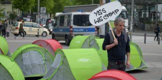 Ein G20-Gegner läuft am 13.05.2017 in Hamburg auf dem Karolinenplatz mit einem Schild mit der Aufschrift «Yes we camp» an Zelten entlang. Der Bezirk Hamburg Nord kann das geplante Camp der Gegner des G20-Gipfels im Stadtpark nicht verbieten.