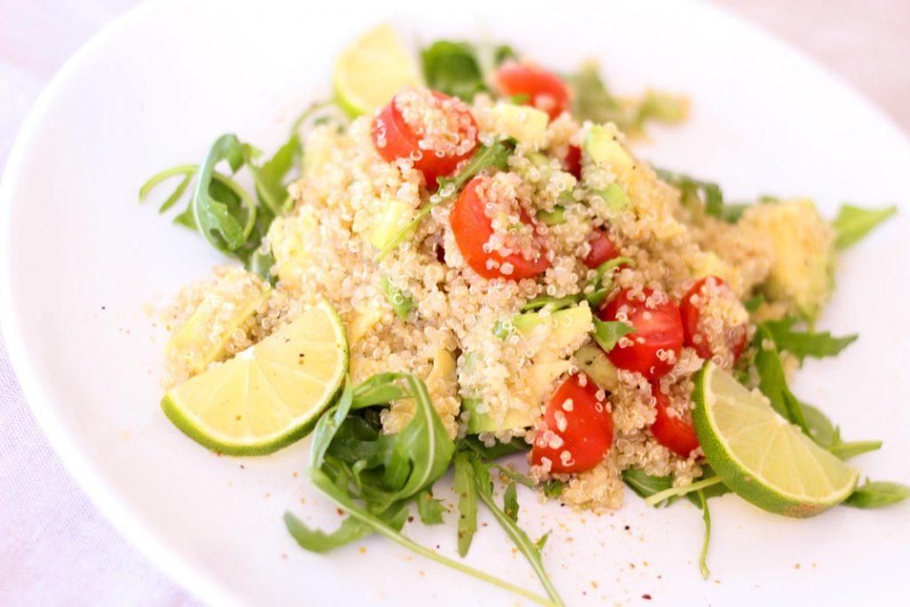 Superfood Quinoa ls Salat auf einem Teller it Kirschtomaten, rucola und Avocado und Limette angerichtet