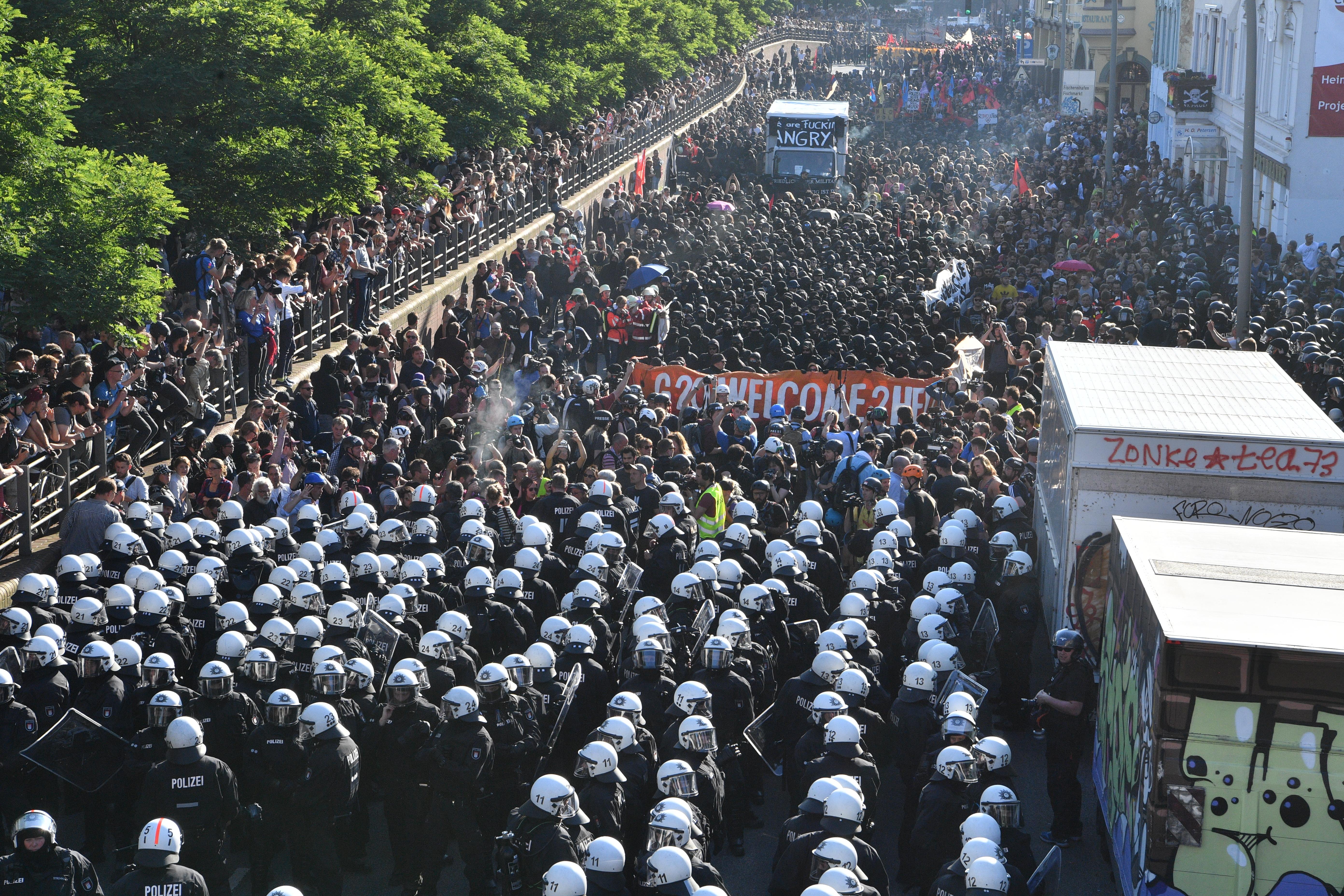 """Demonstranten und Polizisten beim G20-Protestmarsch """"Welcome to hell"""". Foto: Boris Roessler/dpa"""