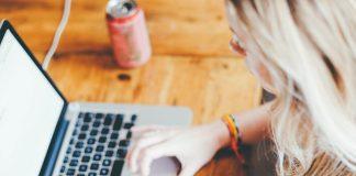 Ein blondes Mädchen sitzt an ihrem Laptop und arbeitet