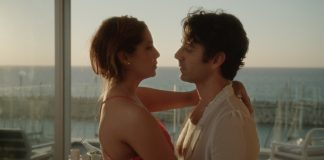 Ein Mann und eine Frau kommen sich in einer Hotelsuite näher. Im Hintergrund Meer.