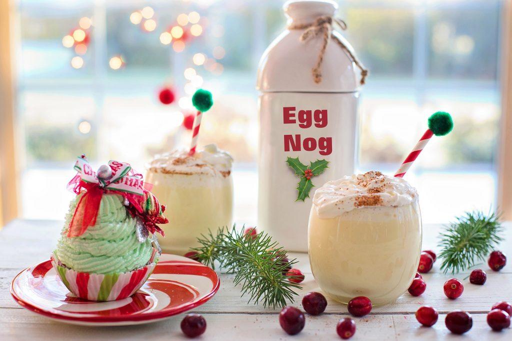 """Eine weie Flasche mit der aufschrift """"Egg Nog"""", zwei mit eierlikör gefüllte Gläser und ein grüner Cupcake auf einem weißen Tisch mit roten Beeren und grünen Tannenzweigen."""