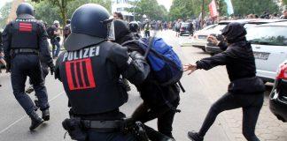 Ein Polizist setzt gegen einen G20-Demonstranten am 07. Juli 2017 einen Schlagstock ein. Foto: Bodo Marks/dpa