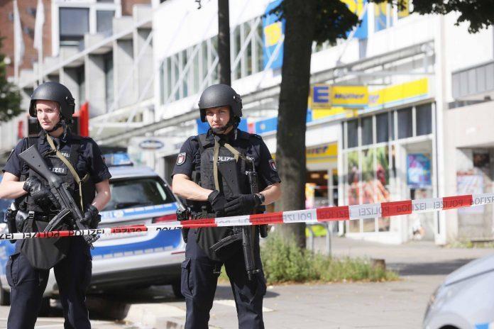 Einsatzkräfte der Polizei sperren am 28.07.2017 nach einer Messerattacke in einem Supermarkt in Hamburg den Tatort ab. Foto: Paul Weidenbaum/dpa