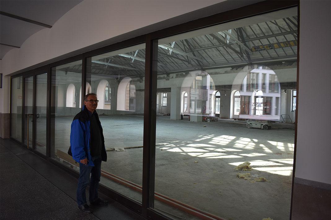 Ein Mann steht vor einer Fensterscheibe, hinter der ein großer leerer Raum ist.