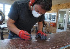 Konzentriert arbeitet Marcel (46) an den Gewinden seines Boards – befreit sie von Metallspänen und Blockaden. Das Werkzeug benutzt er sonst in seiner Zahnarztpraxis, heute bringt er Arbeit und Hobby zusammen. Foto: Hannah Lesch