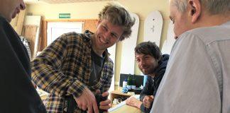 Jannek Grocholl lachend, mit Teilnehmern über dem Kiteboard
