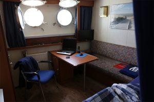 Die Kammer besteht aus einem kleinen Bett, einem Schreibtisch und Waschbecken. Durch zwei Bullaugen kommt Sonnenlicht in das Zimmer. Auf dem Schreibtisch stehen Laptop und Telefon.