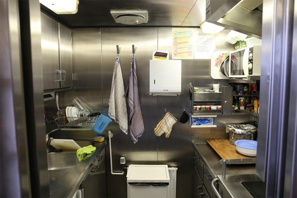Die Küche besteht komplett aus Edelstahl. Tassen hängen an kleinen Haken an der Decke. Ölflaschen und Gewürze stehen hinter einer Leiste im Regal, damit nichts kaputt geht, wenn das Schiff schaukelt.