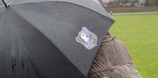 Ein Regenschirm des HFC Falke schützt Fans vor dem Regen.
