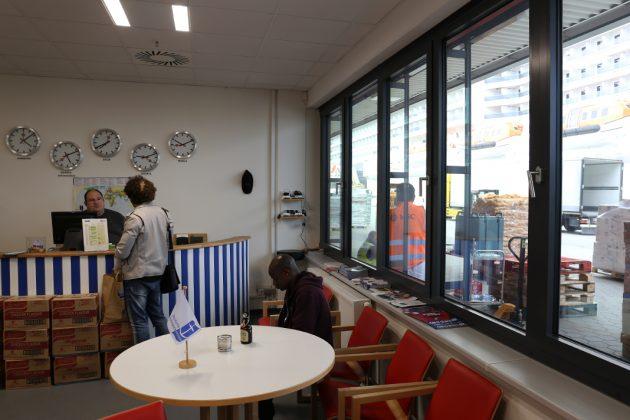 Die Seafarers Lounge für Angestellte auf dem Kreufahrtschiff beinhaltet Bar und Wohnzimmer: Jens Bößiger ist ehrenamtlich tätig und berät einen Seemann über die verschiedenen Tarife der Telefonkarten. Vor den Fenstern liegt eines der Kreuzfahrtschiffe.