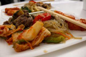 Kimchi, Reiskuchen und Glasnudeln – Koreanische Küche auf Pappschale.