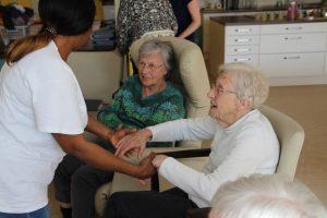 Eine Pflegerin der WPG bittet eine Bewohnerin zum Tanz.