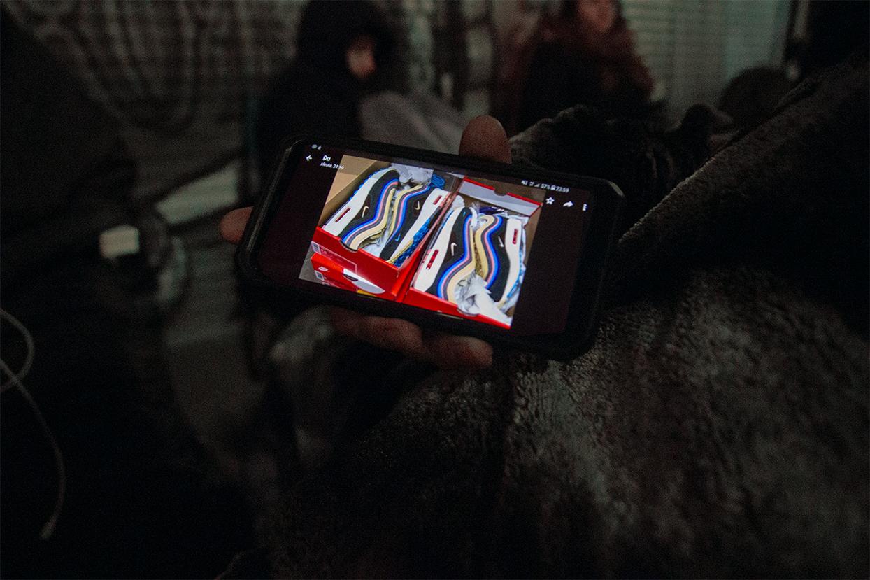 Ein Wartender zeigt die Turnschuhe der Begierde auf seinem Smartphone.