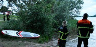 11.06.2018, Hamburg: Einsatzkräfte der Feuerwehr blicken auf den Hohendeicher See, neben ihnen liegt ein Surfbrett. Die Polizei sucht im Hohendeicher See in Hamburg nach einem verunglückten Stand-Up Paddler. Wie ein Polizeisprecher sagte, wird ein 61 Jahre alter Stehpaddler seit Montagabend den 11.06.2016 vermisst. Dessen Freundin sei mit dem Hund des Paares spazieren gegangen, nachdem der Mann aufs Wasser gepaddelt war. Als sie zum See zurückkam, war der Mann nicht mehr auf dem Wasser zu sehen. Ein Großaufgebot von Polizei und Feuerwehr suchte rund zweieinhalb Stunden nach dem Mann, auch ein Hubschrauber war im Einsatz. Sein Surfbrett und ein Paddel wurden gefunden, wie der Sprecher sagte. «Von der Person fehlt noch jede Spur.»