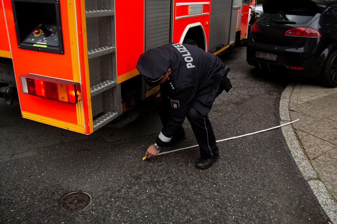 Ein Feuerwehrmann markiert mit Kreide den Abstand eines geparkten Autos zum Feuerwehrwagen.