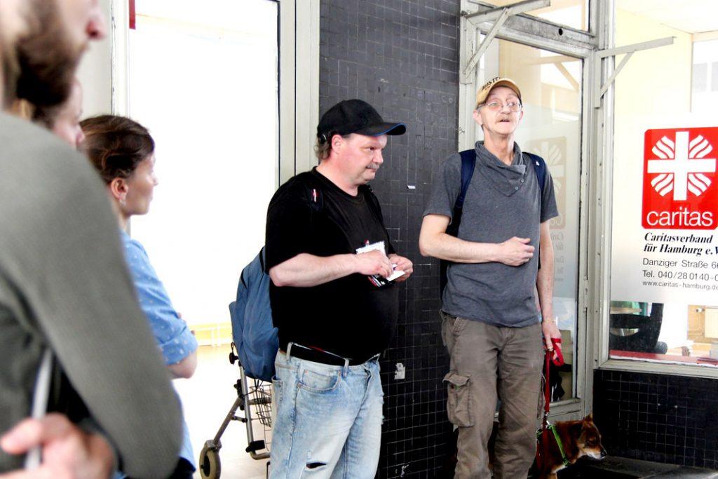 Chris und Harald stehen vor dem alten Gebäude des Stützpunkts der Caritas. Hier können Obdachlose Schließfächer nutzen.