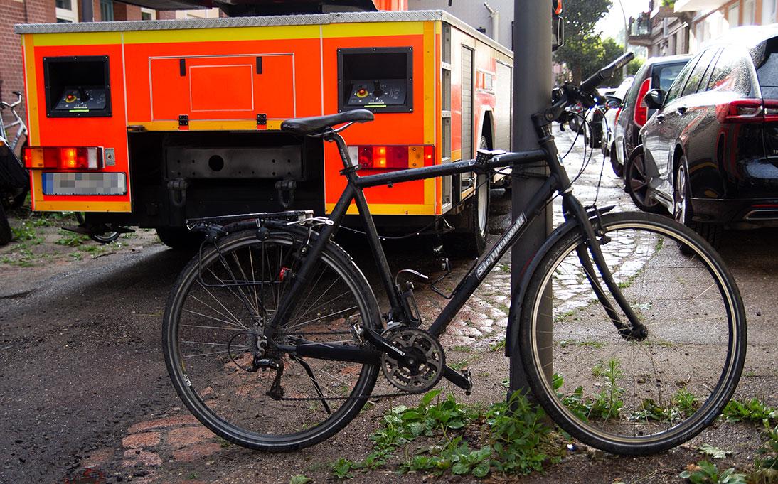 Ein Fahrrad steht quer auf der Fahrbahn und blockiert den Feuerwehrwagen.