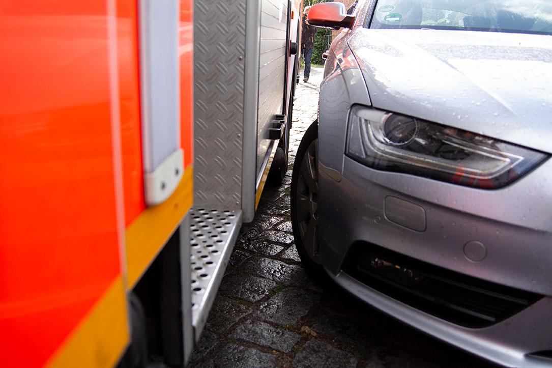 Ein Feuerwehrwagen steht sehr nah neben einem geparkten Auto und kommt nicht vorbei.