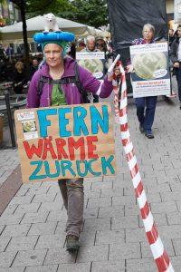 """Die Demonstrantin Helene Hohmeier von """"NaturFreunde Hamburg"""" (l), trägt ein Transparent mit der Aufschrift: """"Fernwärme zurück"""" und zieht zusammen mit weiteren Demonstranten durch die Spitalerstraße. Geschätzt etwa 300 Menschen haben für den Rückkauf des Fernwärmenetzes demonstriert. Foto: Georg Wendt/dpa"""