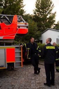 """Feuerwehrmänner warten auf den Abschleppwagen bei der Aktion """"Platz für Retter""""."""
