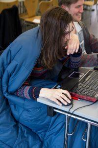 Eine Studentin sitzt beim HAW Game Jam im Schlafsack vor ihrem Computer.