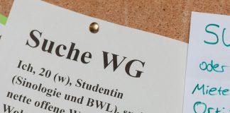 Studentinnen suchen mit Zetteln an einem Schwarzen Brett eine Wohnung.