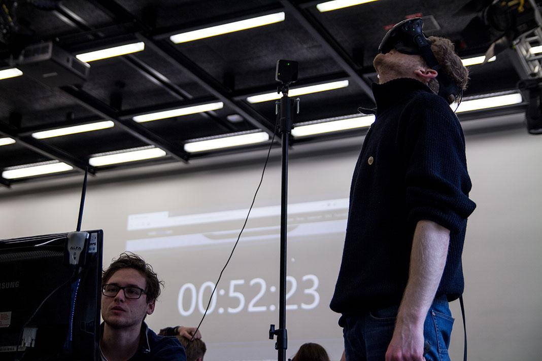Ein Teilnehmer des HAW Game Jam trägt eine VR-Brille. Im Hintergrund läuft ein Countdown.