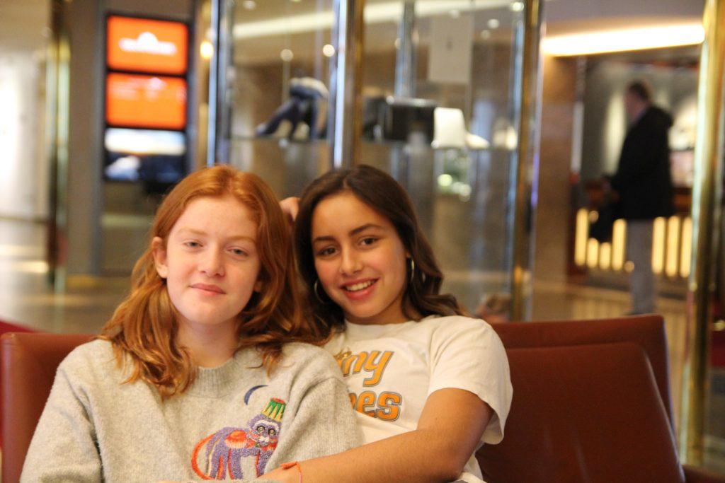 Auch im Film verstehen die beiden angehenden Wildhexen Clara und Kahla sich gut und helfen sich. Die beiden jungen Schauspiellerinnen von Wildhexe sitzen arm in arm aud dem Sofa und lächeln.
