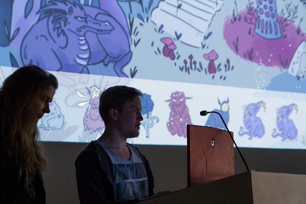 Zwei TeilnehmerInnen des HAW Game Jam stehen auf dem Podium. Hinter wird eine Spielszene mit dem Beamer an die Wand projiziert.