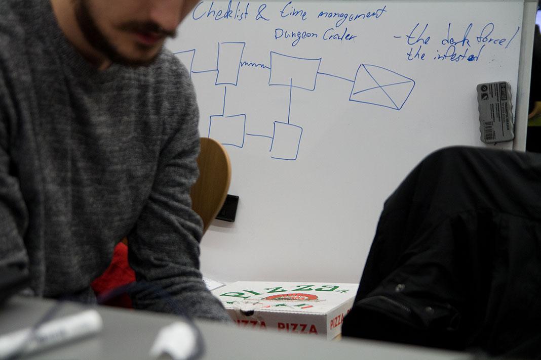 Hinter einem Teilnehmer des HAW Game Jam steht ein Whiteboard mit aufgezeichnetem Level-Plan. Davor liegt eine Pizza-Schachtel.