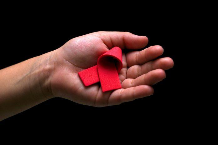 Hand mit roter HIV/AIDS-Schleife