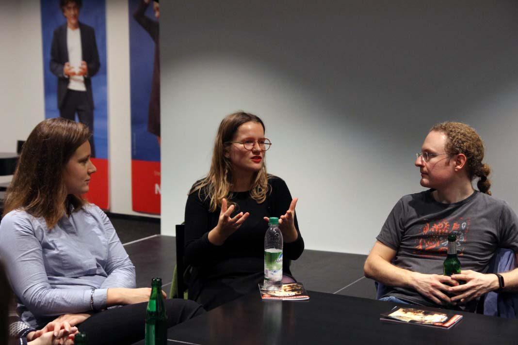 Uni trifft Theater. Eine Teilnehmerin sitzt in der Runde und diskutiert mit den Schuaspieler*innen über das Stück. Foto: Nadine von Piechowski