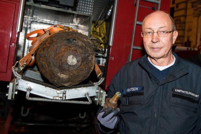 Burkhard Mantsch, Sprengmeister des Kampfmittelräumdienstes, steht neben einer entschärften Fliegerbombe.