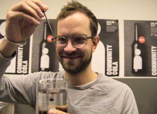 Jan van Schwamen tropft Zuckerkulör für die Community Cola in ein Glas mit Wasser.