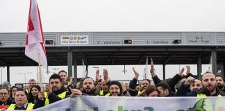 Mitglieder der Gewerkschaft Verdi stehen mit Fahnen vor dem Flughafen. An den Airports Köln/Bonn, Düsseldorf und Stuttgart findet ein ganztägiger Warnstreik des Sicherheitspersonals statt. Foto: Federico Gambarini/dpa