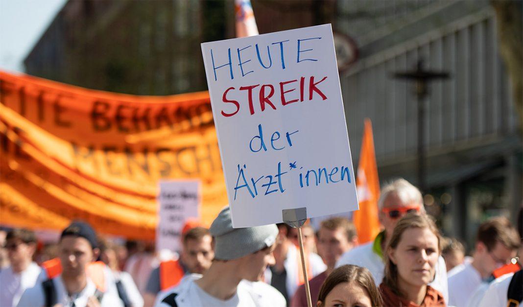 Eine Frau trägt ein Plakat mit der Aufschrift