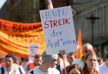 """Eine Frau trägt ein Plakat mit der Aufschrift """"Heute Streik der Ärzt*innen""""."""