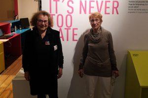 """Die beiden Senior-Guides Barbara Greulich und Ute Zäpernick stehen in der Ausstellung vor einer Wand mit dem Schriftzug """"It's never too late""""."""
