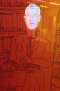 Auf einer Leinwand ist ein männlicher Körper im Anzug gezeichnet. Der Kopf des Mannes ist digital darauf projiziert und spricht.