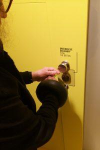 An einer Station der Ausstellung wird Tremor simuliert. Barbara Greulich steht vor einer gelben Tür und versucht, eine Haustür aufzuschließen.