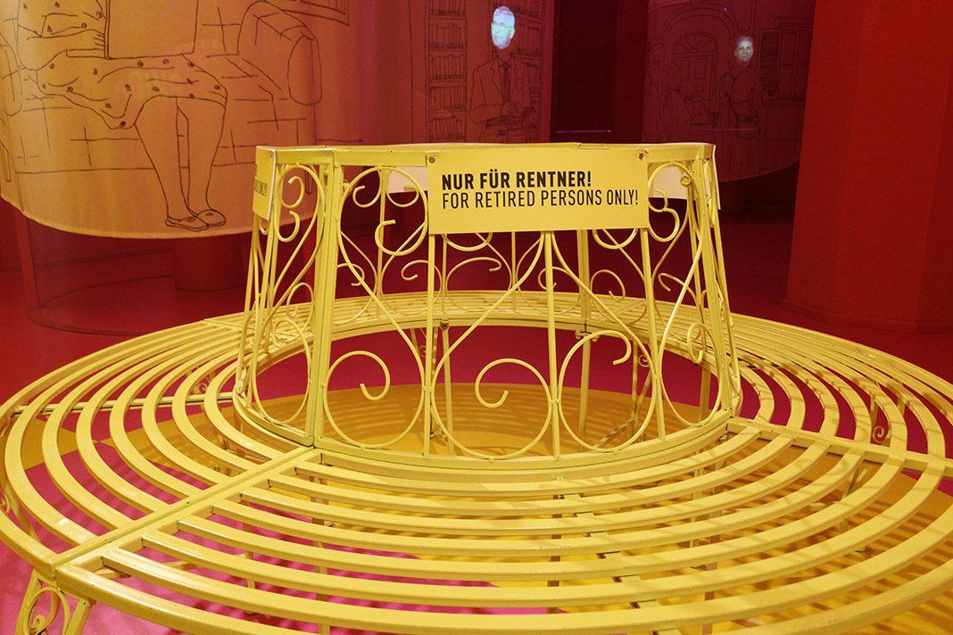 Eine gelbe Bank steht in der Mitte des Raumes. Auf einem Schild steht:
